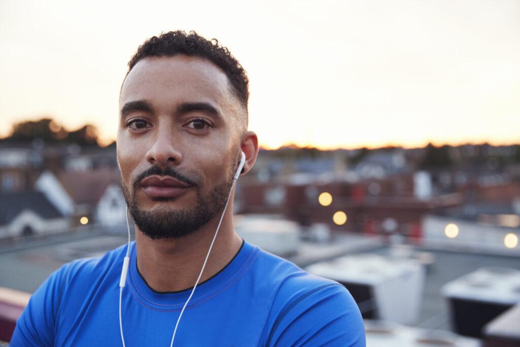 Man with earphones in front of skyline